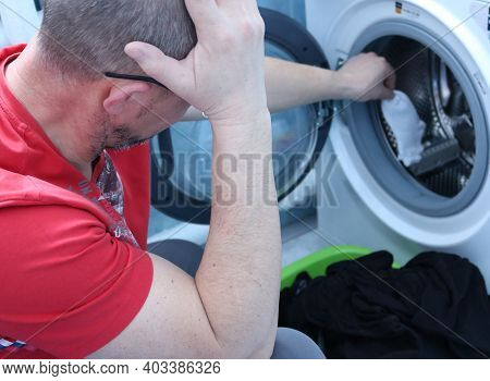 A Man In A Home Laundry In A Panic Clutched His Head From An Accidental Incorrect Washing Of Clothes