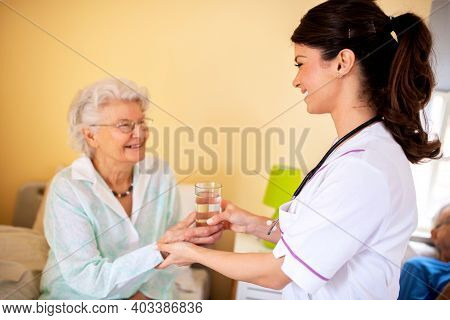 Lady Doctor Handing A Glass Of Water To Elder Woman Nursing Home Occupant