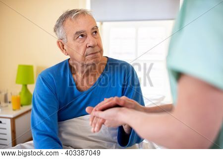 Caring Nurse Holding A Hand Of A Senior Man Occupant In A Nursing Home Room