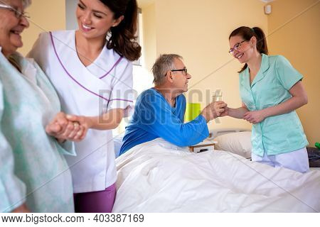 Senior Man And Senior Woman Nursing Home Residents Assisted By Medical Staff Of The Residential Faci