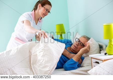 Elder Man Resident Of A Nursing Home Sleeping While Medical Staff Nurse Is Covering Him With Sheet,