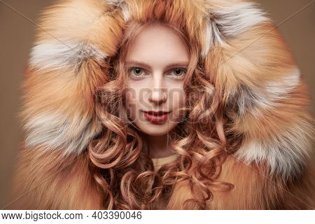 Portrait of a beautiful young woman with long red hair posing in a luxurious fox fur coat. Fur coat fashion.