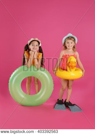 Cute Little Children In Beachwear With Bright Inflatable Rings On Pink Background