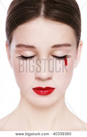 Close-up portrait of young beautiful girl crying with bloody tears, on white background