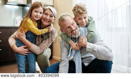 Happy Family, Grandparent With Grandchildren Spending Time Together, Hugging And Smiling At Camera W