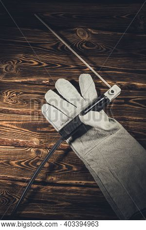 The Holder Of The Welding Electrode With An Electrode, Lie In A Welding Glove On A Wooden Background