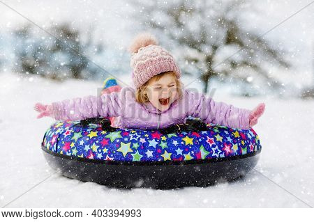Active Toddler Girl Sliding Down The Hill On Snow Tube. Cute Little Happy Child Having Fun Outdoors