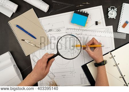 Look Through A Magnifying Glass. Mechanical Drawing On Sheets Of Paper. Hands On The Table Top View.