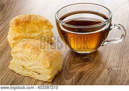 Two Puff Cookies, Transparent Cup With Tea On Brown Wooden Table