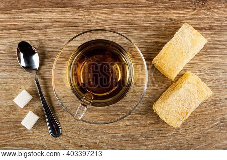 Sugar Cubes, Teaspoon, Transparent Cup With Tea On Saucer, Two Puff Cookies On Brown Wooden Table. T