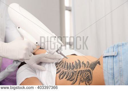 Young Woman Undergoing Laser Tattoo Removal Procedure In Salon, Closeup