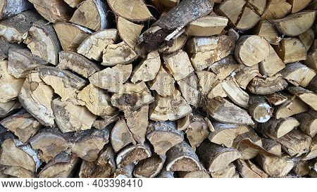 Logs Of Firewood Lie One To One In A Woodshed Close-up. Village Life In Winter. Logs Of Firewood For