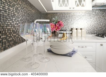 Beautiful Ceramic Dishware And Glasses On Countertop In Modern Kitchen