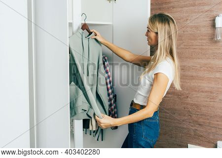 Stylish Young Woman In The Wardrobe Chooses What To Wear From The Wardrobe.