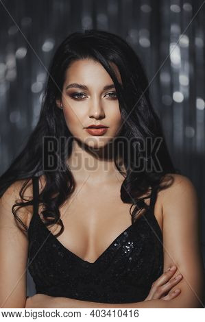 Stunning Celebrating Woman In The Black Shiny Dress. Confident Brunette Girl Portrait With Perfect M