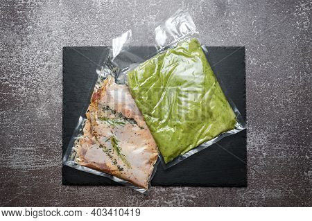 Products In Vacuum Packaging On Black Slate Board. Chicken Meat With Herbs And Green Beans Puree, Va
