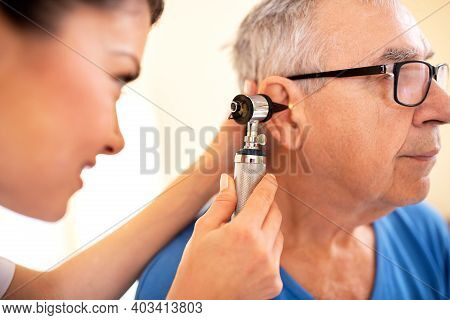 Doctor Using Otoscope To Check On Elder Mans Ear