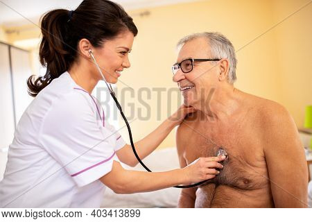 Woman Doctor Providing Care In Nursing Facility To A Senior Man, Medically Assisting Others Concept
