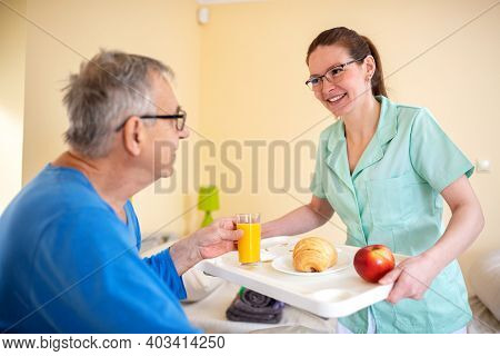 Breakfast In Bed, Residential Care In A Nursing Home, Elder Man Nursing Home Occupant Being Served B