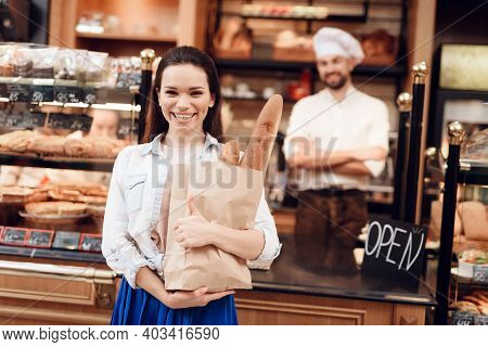 Young Smiling Woman Buying Bread In Modern Bakery.