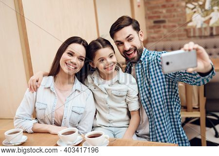 Young Happy Family Taking Selfie In Cafeteria.
