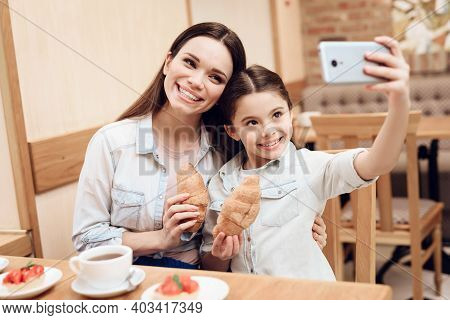 Mother With Daughter Taking Selfie In Cafeteria.