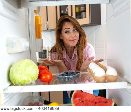 Pretty Woman Looking At Her Groceries In The Refrigerator, Especially Cabbage
