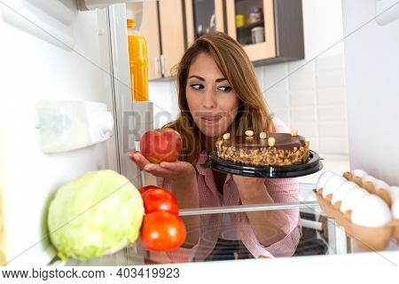 Brunette Young Woman Choosing Between An Apple And A Cake
