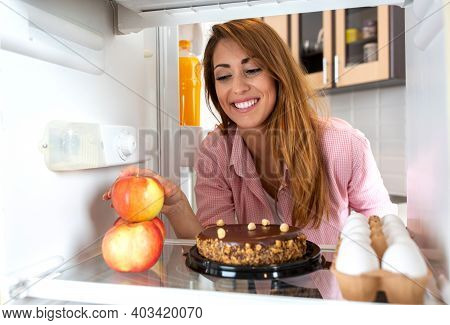 Inside Of A Fridge View Concept Of Young Woman Choosing Between Apples And A Cake