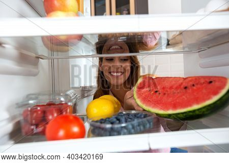Smiling Face Lurking Between The Shelves Of A Refrigerator Full With Healthy Foods