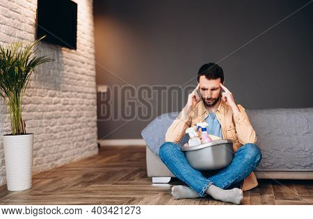 Stressed Man Looking Disappointed Before Housecleaning, Sitting On Floor With Cleaning Supplies, Cop