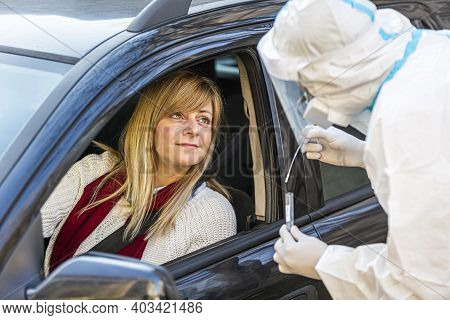 Woman Sitting In Car, Waiting For Medical Worker To Perform Drive-thru Covid-19 Test, Taking Nasal S