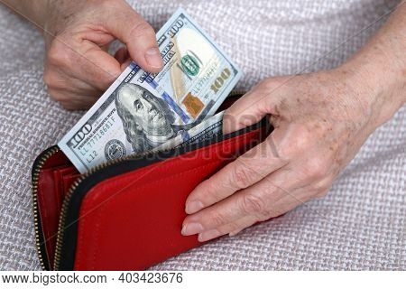 Elderly Woman Takes Out Us Dollars From Her Wallet. Concept Of Pension Payments, Savings At Retireme