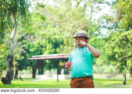 Boy Wearing A Hat Blowing Bubbles In The Park