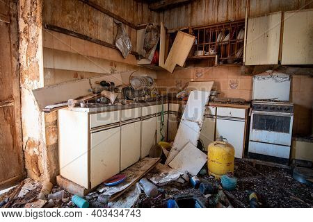 Abandoned And Destroyed Kitchen House Room With Damaged Furniture And Kitchenware. Abandon Places In