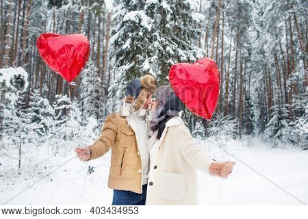 Winter Couple In Love. A Boy And A Girl Embrace In The Winter Snow And Fairy Forest. Valentines Day