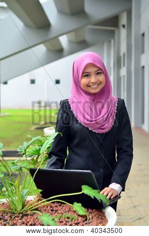 Close-up portrait of beautiful young Asian student with laptop