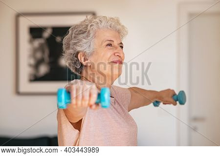 Senior woman lifting weights and working out at home. Old woman doing arms stretching exercise using weight dumbbells. Retired lady exercising with light weights.