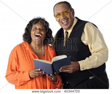 A senior African American couple sing together from a songbook.  On a white background.