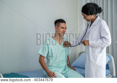 The African American Doctor Is Checking The Symptoms By Checking The Patient's Heart On The Patient'