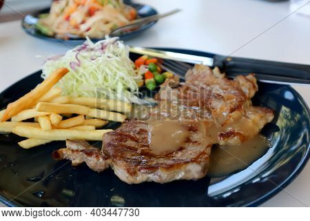 Pork Steak With French Fries And Vegetable