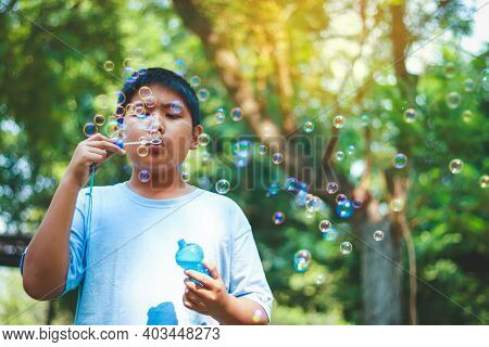 An Asian Boy Is Playing Blowing Bubbles In The Park.