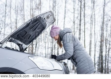 Car Repair On The Road In Winter. Young Girl Is Trying To Fix A Car Breakdown Under The Soot On The