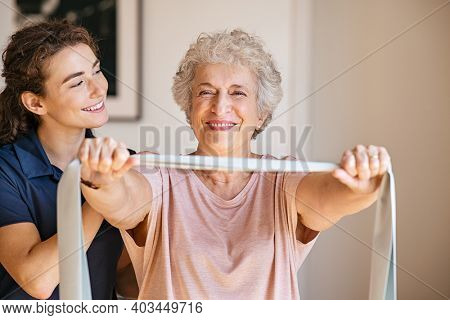 Personal trainer assisting senior woman with resistance band. Rehabilitation physiotherapy worker helping old patient at nursing home. Old woman with stretch band being coached by physiotherapist.