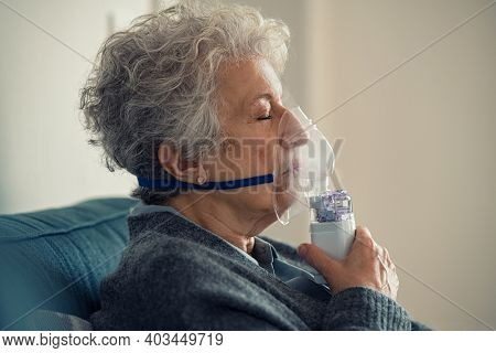 Ill senior woman making inhalation at home. Close up of an elderly woman holding mask nebulizer inhaling fumes medication into lungs. Self treatment of the respiratory tract using inhalation nebulizer