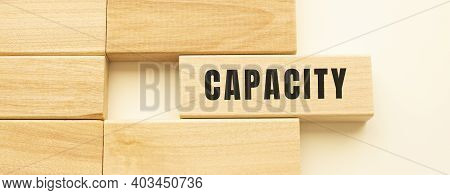 Capacity Text On A Strip Of Wood Lying On A White Table. Concept.