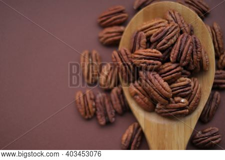 Pecan Nut In Spoon On Bright Brown Background.healthy Fats.heap Shelled Pecans Nut Closeup. Ingredie