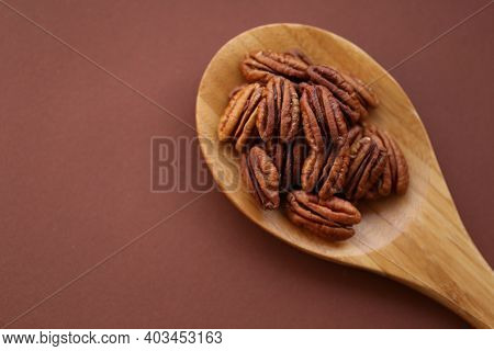 Pecan Nut Close-up In Spoon On Bright Brown Background.healthy Fats.heap Shelled Pecans Nut Closeup.