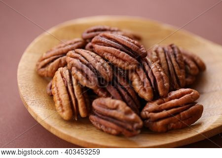 Pecan Nut Close-up In Spoon On Brown Background.healthy Fats.heap Shelled Pecans Nut Closeup. Ingred
