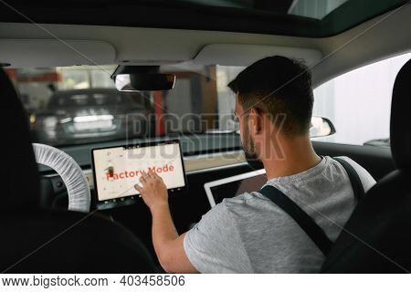 Young Caucasian Man Doing Diagnostics Of Electric Auto Using On-board Computer On Car Service Statio